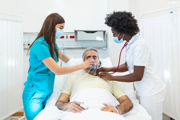 Junger arzt und krankenschwester, die eine chirurgische maske tragen, die einen älteren männlichen patienten prüft, der eine überdrucksauerstoffmaske trägt, um das atmen in einem krankenhausbett zu unterstützen