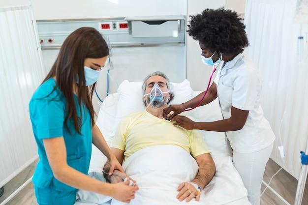 Junger arzt und krankenschwester, die eine chirurgische maske tragen, die einen älteren männlichen patienten prüft, der eine überdrucksauerstoffmaske trägt, um die atmung in einem krankenhaus zu unterstützen