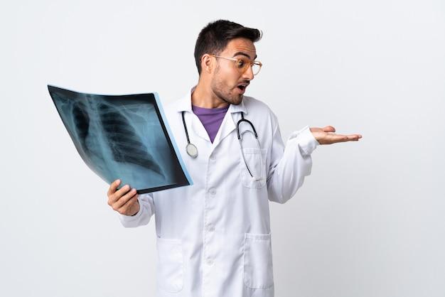 Junger arztmann, der eine radiographie lokalisiert auf weißer wand hält, die imaginären copyspace auf der handfläche hält