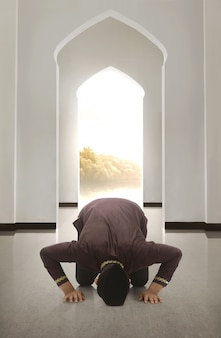 Junger asiah moslemischer mann mit schutzkappe betend