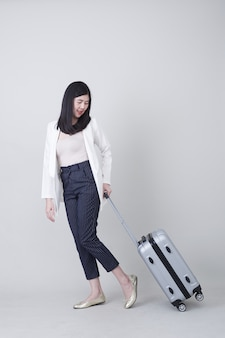 Junger asiatintourist mit dem gepäck zu reisen