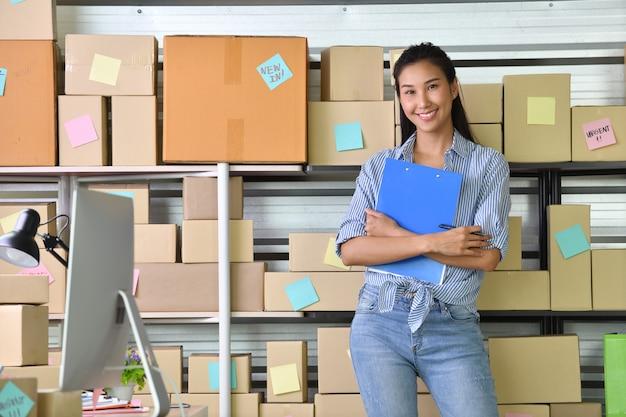 Junger asiatinunternehmer geschäftseigentümer, der zu hause für das on-line-einkaufen arbeitet und paketprodukt vorbereitet