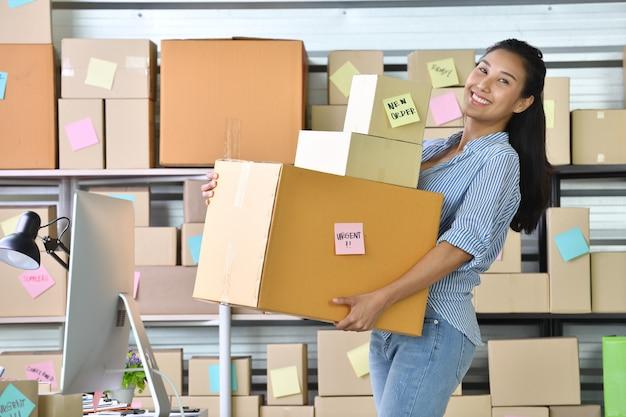Junger asiatinunternehmer / geschäftseigentümer, der zu hause für das on-line-einkaufen arbeitet und paketprodukt vorbereitet