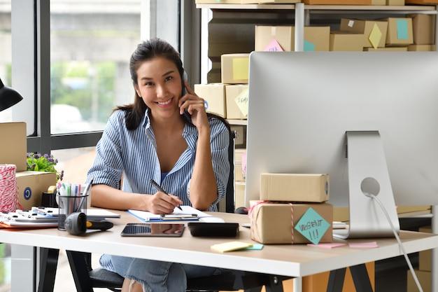 Junger asiatinunternehmer geschäftseigentümer, der zu hause mit computer arbeitet