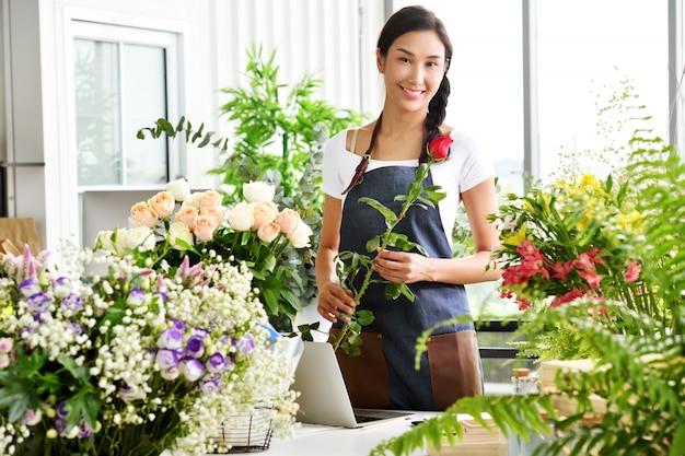 Junger asiatinunternehmer / ladenbesitzer / florist eines kleinen blumenladengeschäfts