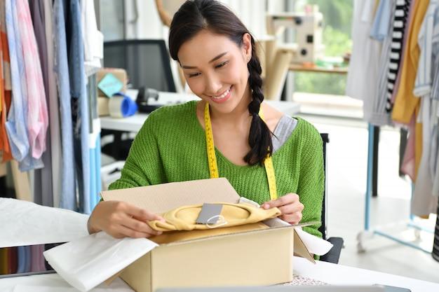 Junger asiatinunternehmer / modedesigner, der im studio arbeitet und produkt verpackt und sendet