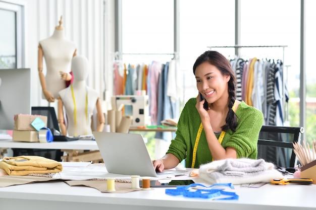 Junger asiatinunternehmer / modedesigner, der im studio arbeitet