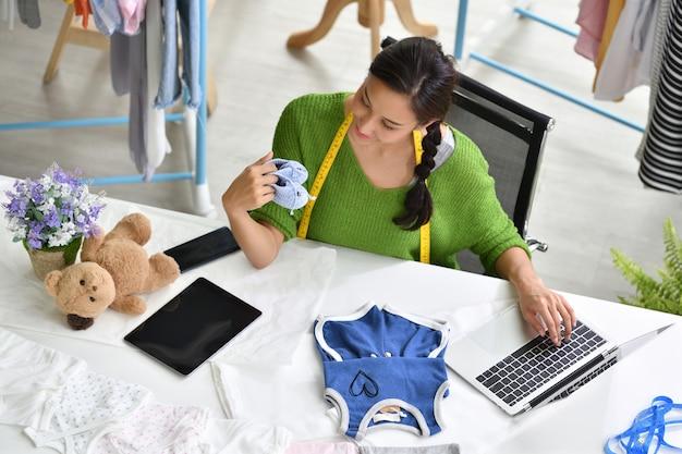 Junger asiatinunternehmer / modedesigner für die babykleidung, die im studio arbeitet