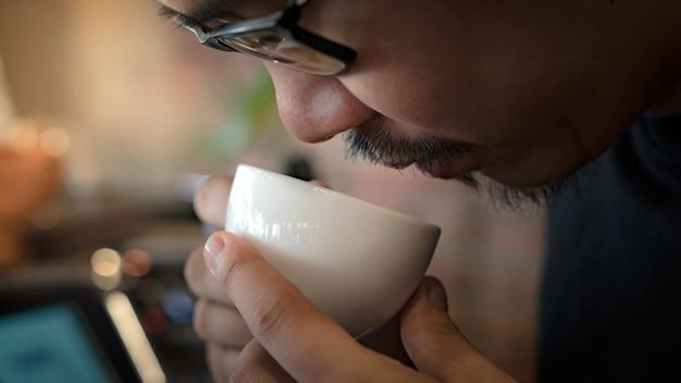 Junger asiatischer barista mann, der keramikbecher nahe an seiner nase hält