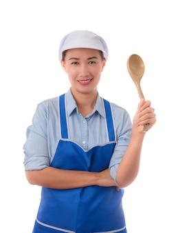Junger asiatischer chef, überzeugte haltung der hausfrau und halten einer spachtel im schutzblech, halbes porträt
