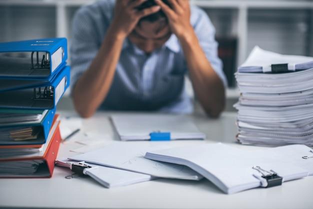 Junger asiatischer erschöpfter geschäftsmann mit unordentlichem schreibtisch und stapel von papieren, beschäftigt beschäftigt, überarbeitet.