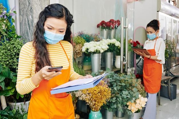 Junger asiatischer florist in der medizinischen maske, die textnachrichten und benachrichtigungen auf dem smartphone prüft, wenn ihr mitarbeiter bestellung für kunden arrangiert