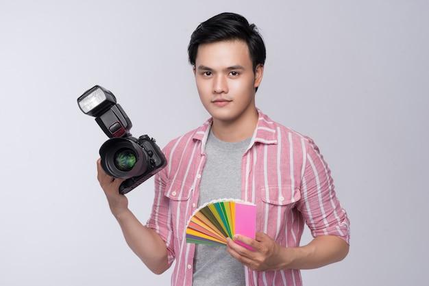 Junger asiatischer fotograf, der eine digitalkamera und eine farbprüfkarte und eine farbpalette hält, während er im studio arbeitet