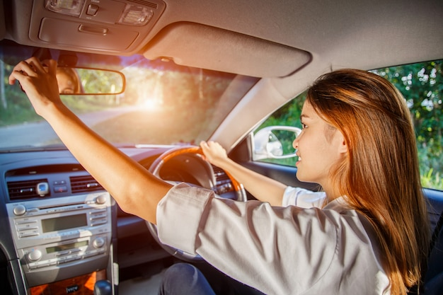 Junger asiatischer frauenfahrer, der ihren rückspiegel im auto justiert.