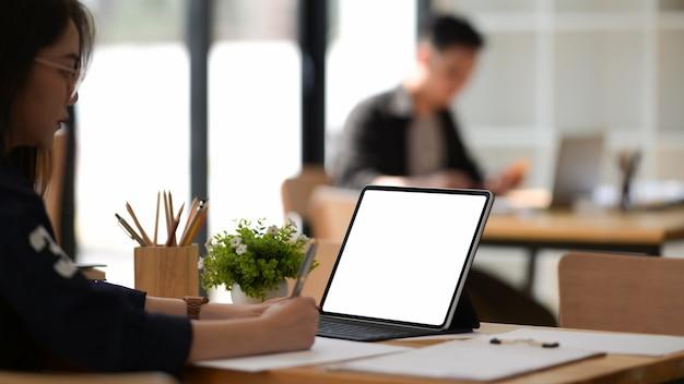 Junger asiatischer frauenfreiberufler, der mit laptop arbeitet