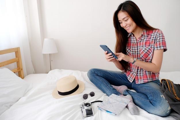 Junger asiatischer frauenreisender, der karte und smartphone beim sitzen auf bett hält