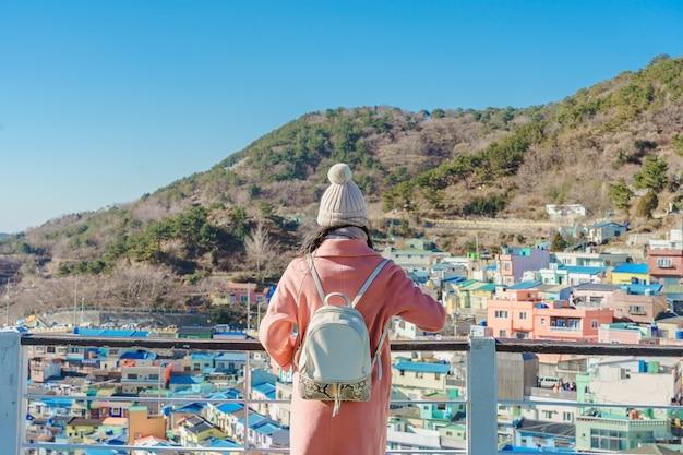 Junger asiatischer frauenreisender mit dem rucksack, der in das gamcheon kultur-dorf gelegen in busan, südkorea reist