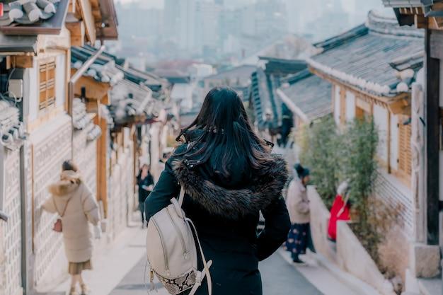 Junger asiatischer frauenreisender mit dem rucksack, der in die traditionelle koreanische artarchitektur reist