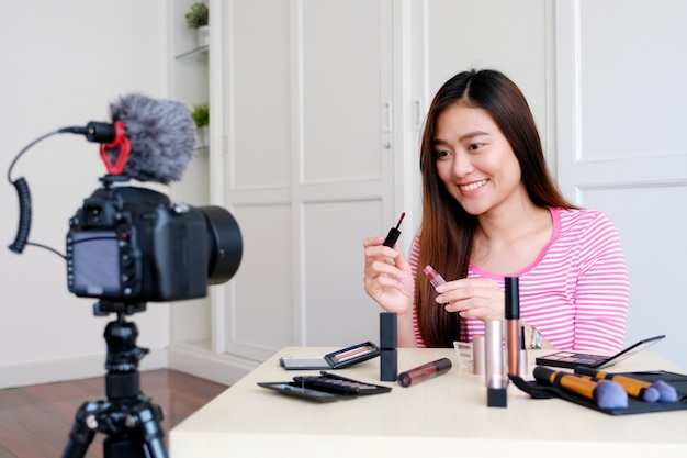 Junger asiatischer frauenschönheit blogger, der kosmetik beim aufzeichnen zeigt, wie man videotutorial durch kamera bildet