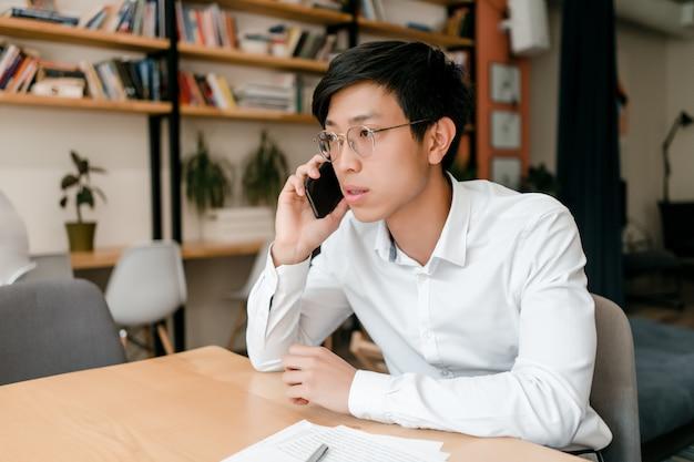 Junger asiatischer geschäftsmann, der am telefon bespricht geschäft im büro spricht