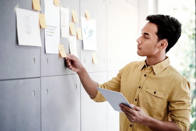 Junger asiatischer geschäftsmann, der an digital-tablet im büro-konferenzzimmer arbeitet