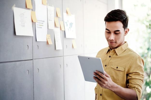 Junger asiatischer geschäftsmann, der an digital-tablet im büro-konferenzzimmer arbeitet.