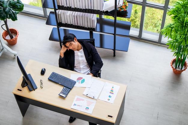 Junger asiatischer geschäftsmann, der auf einem stuhl in einer bequemen position im büro sitzt