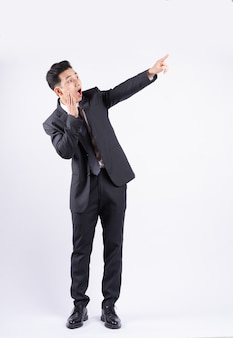 Junger asiatischer geschäftsmann, der auf weiß steht