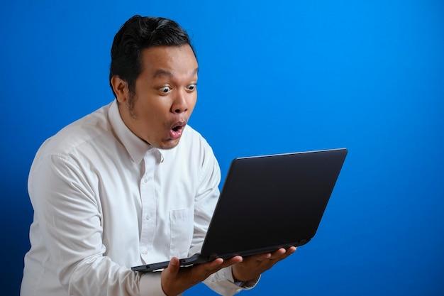 Junger asiatischer geschäftsmann, der beiläufiges weißes hemd trägt und laptop betrachtet, überraschter ausdruck. körperporträt hautnah