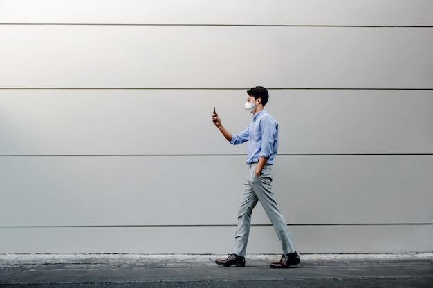 Junger asiatischer geschäftsmann, der eine chirurgische maske trägt und ein smartphone beim gehen durch die städtische gebäudewand verwendet.