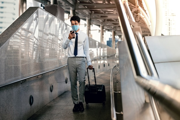 Junger asiatischer geschäftsmann, der eine chirurgische maske trägt und ein smartphone beim gehen verwendet