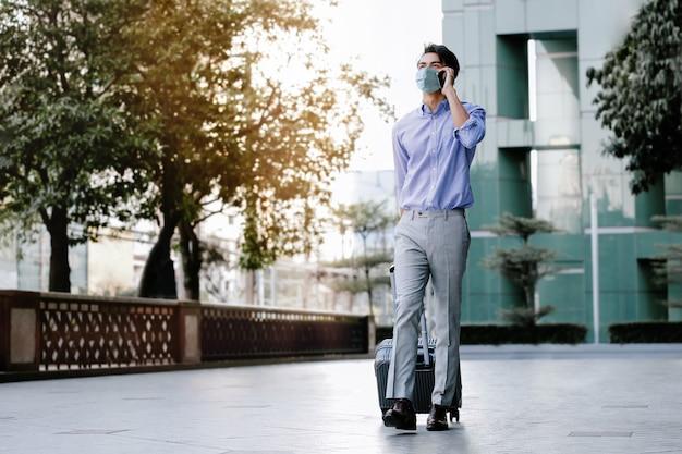 Junger asiatischer geschäftsmann, der eine chirurgische maske trägt und ein smartphone benutzt, während er mit koffer in der stadt geht