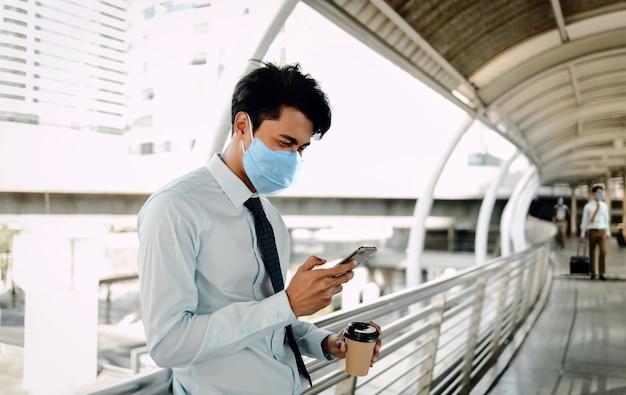 Junger asiatischer geschäftsmann, der eine chirurgische maske trägt und ein smartphone in der stadt benutzt.