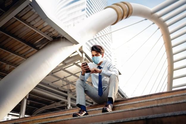 Junger asiatischer geschäftsmann, der eine chirurgische maske trägt und ein smartphone in der stadt benutzt