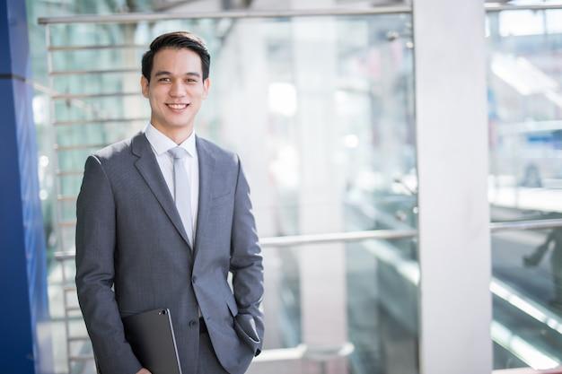Junger asiatischer geschäftsmann, der eine tablette hält