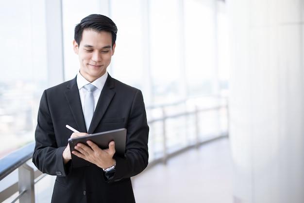Junger asiatischer geschäftsmann, der eine tablette schaut schirm hält