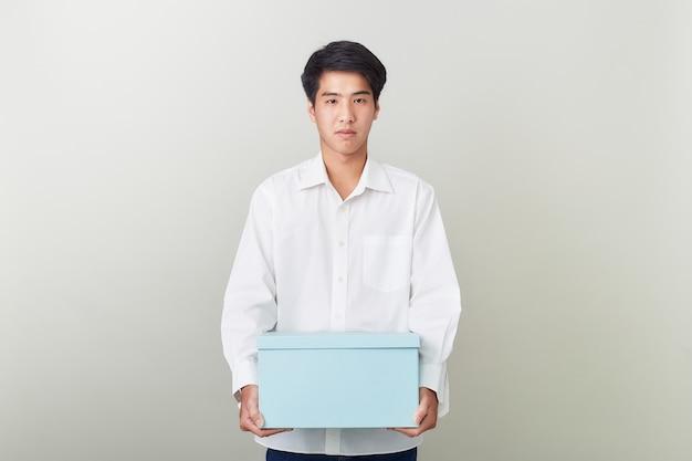 Junger asiatischer geschäftsmann, der einen kasten anhält