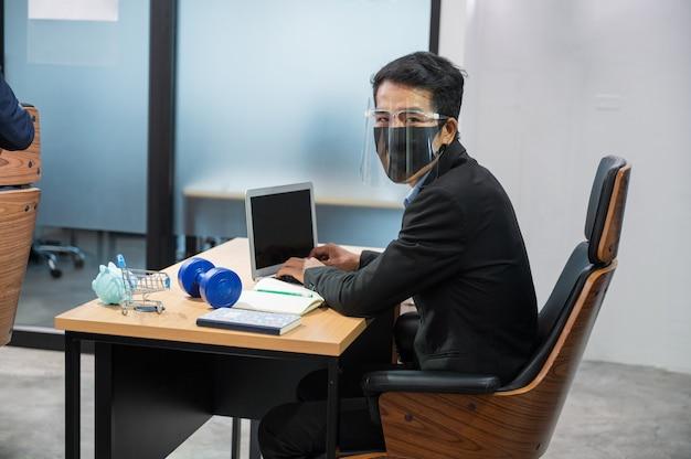 Junger asiatischer geschäftsmann, der gesichtsschutz trägt kamera betrachtet und mit laptop und sparschwein, kurzhantel, wagen und notizbuch am schreibtisch im büro arbeitet
