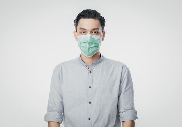 Junger asiatischer geschäftsmann, der hygienemaske trägt, um infektion, 2019-ncov oder coronavirus zu verhindern. luftbedingte atemwegserkrankungen wie pm 2.5-kämpfe und grippe an der weißen wand