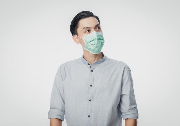 Junger asiatischer geschäftsmann, der hygienemaske trägt und nach oben schaut, um infektion, 2019-ncov oder coronavirus zu verhindern. luftbedingte atemwegserkrankungen wie pm 2.5-kämpfe und grippe an der weißen wand