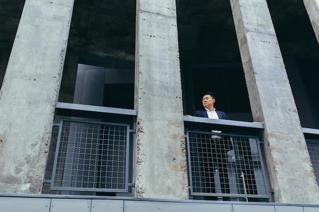Junger asiatischer geschäftsmann, der in der nähe eines modernen schwarzen bürogebäudes aus beton steht, auf der balkonterrasse mit säulen