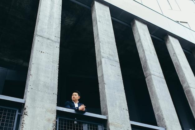 Junger asiatischer geschäftsmann, der in der nähe eines modernen schwarzen bürogebäudes aus beton steht, auf der balkonterrasse mit säulen Premium Fotos