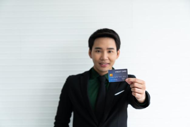 Junger asiatischer geschäftsmann, der kreditkarte auf weiß hält