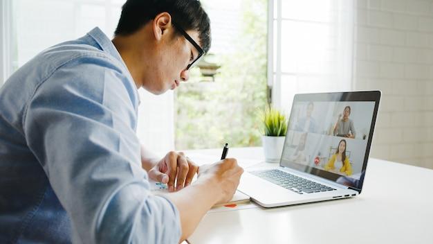 Junger asiatischer geschäftsmann, der laptop verwendet, spricht mit kollegen über plan in videoanrufbesprechung, während arbeit von zu hause im wohnzimmer. selbstisolation, soziale distanzierung, quarantäne zur vorbeugung von koronaviren.