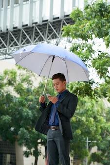 Junger asiatischer geschäftsmann, der mit regenschirm in der straße steht und smartphone verwendet