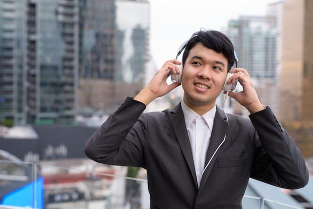 Junger asiatischer geschäftsmann, der musik gegen ansicht der stadt hört