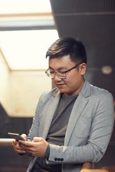 Junger asiatischer geschäftsmann, der smartphone im büro verwendet