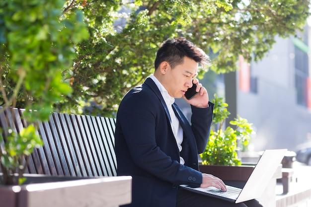 Junger asiatischer geschäftsmann, freiberufler, der auf einer bank sitzt und mit laptop im stadtpark auf modernem städtischen straßenhintergrund im freien in der innenstadt arbeitet