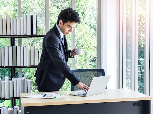Junger asiatischer geschäftsmann im anzug, der heißen kaffeetasse steht und hält und auf laptop-computer im büro schaut