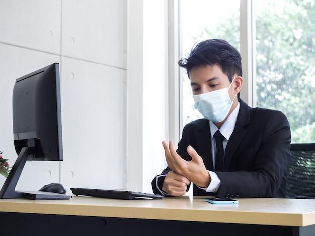 Junger asiatischer geschäftsmann im anzug, der medizinische gesichtsmaske trägt, die handschmerzen erhält, während notebook-computer im büro verwendet